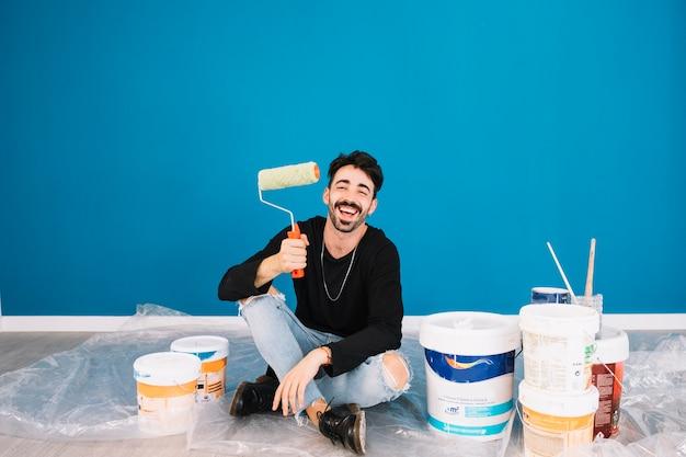 Улыбающийся человек, показывая рулон краски