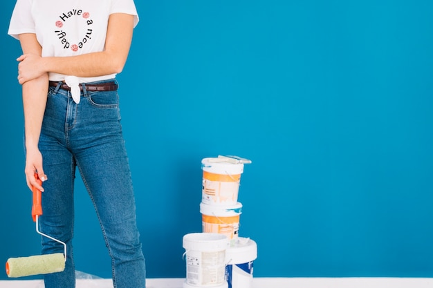 Девушка, стоящая рядом с красками ведра