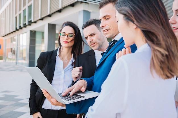 Вид сбоку бизнес-команды с ноутбуком