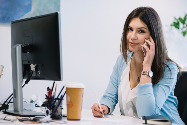 Женщина с телефоном и глядя на камеру