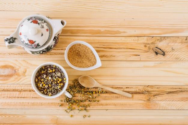 Сахар и чайник рядом с ромашковым чаем