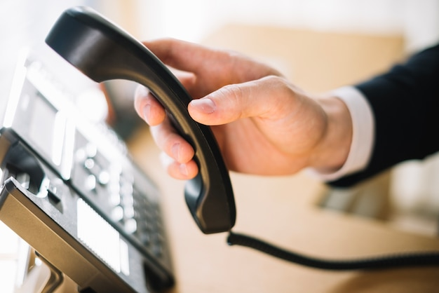 オフィスで電話を使っている男