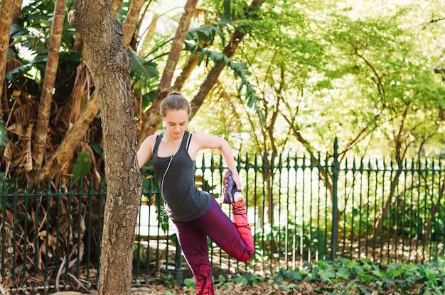 Женщина, растяжение ноги возле дерева