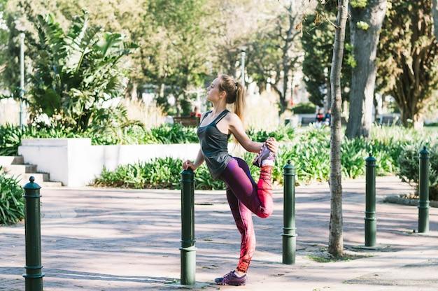 Женщина растяжения ноги в парке