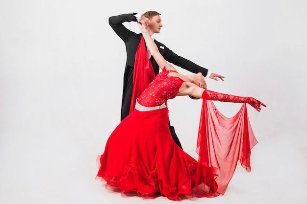 白い背景で踊っているカップル