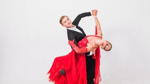 ボールルームのダンスの動きを行っているカップル