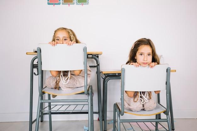 面白い女の子が椅子の後ろから覗く