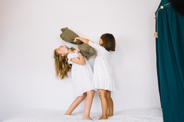 女の子同士で枕を打つ