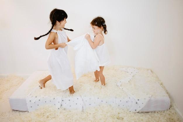 女の子は枕でマットレスにジャンプ