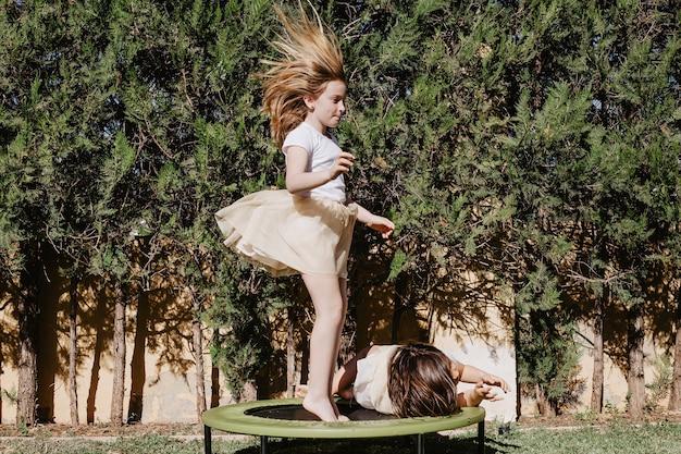 横たわっている妹の近くでトランポリンに飛び乗る女の子