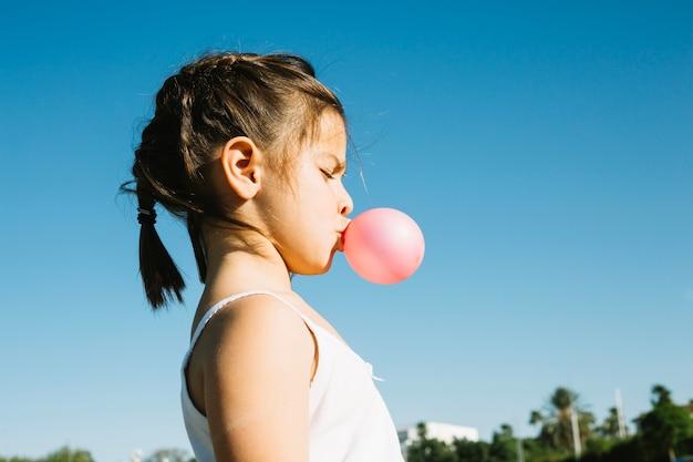 バブルガムを吹くかわいい女の子