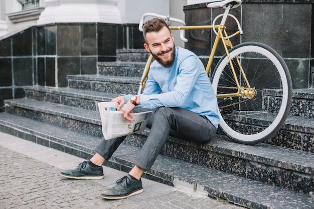 階段に座っている新聞を持った陽気な男