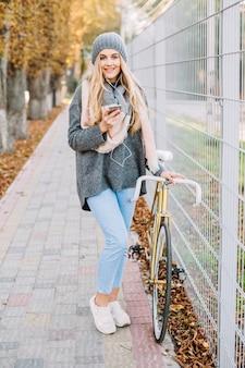 女性、スマートフォン、自転車でポーズをとる