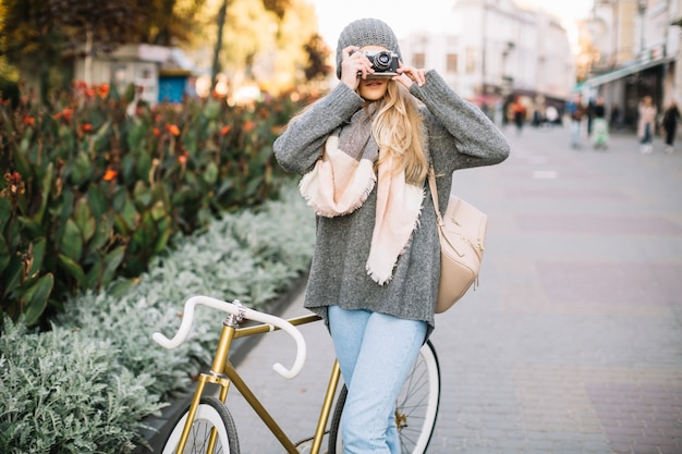 写真を撮っている自転車を持つ女性