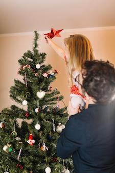 クリスマスツリーに星を置く家族