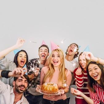 Молодые друзья с тортом на день рождения