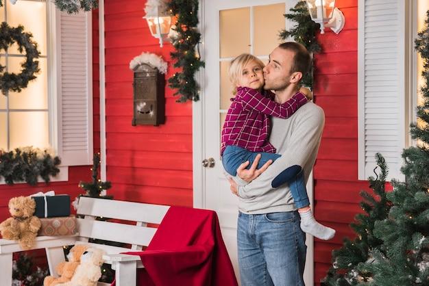 家の前でクリスマスに娘と父親