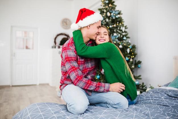 クリスマスのベッドで抱き合っているカップル