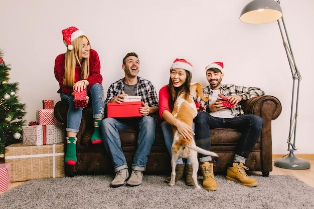 Рождественский подарок концепции с четырьмя друзьями на диване и собака