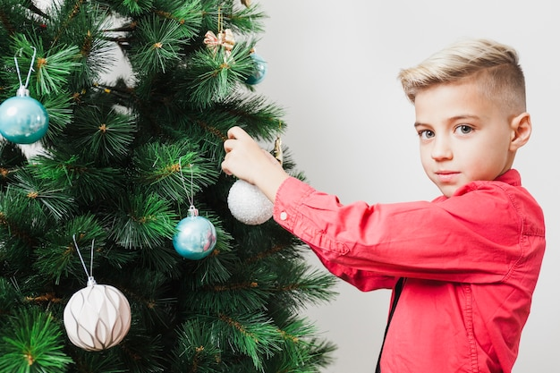クリスマスツリーを飾る若い少年
