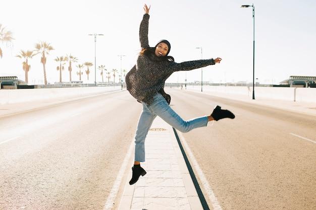 ストリートの真ん中でジャンプする楽しい女性