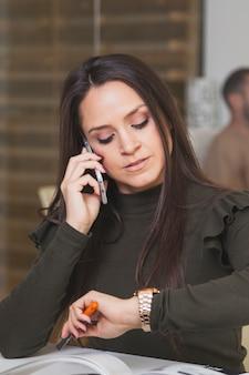 電話で話して時間を見ている女性