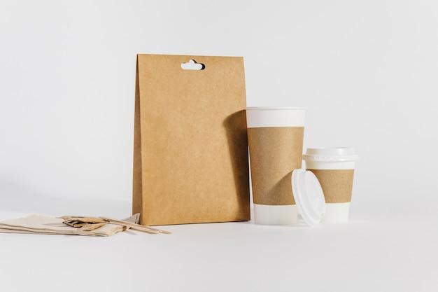 Две пластиковые чашки рядом с сумкой