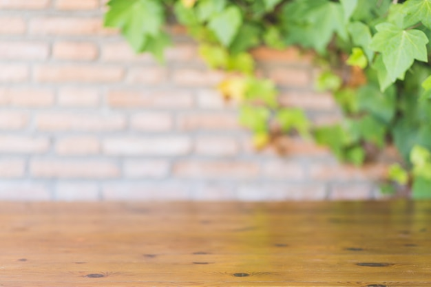 Деревянная столешница возле кирпичной стены и виноградной лозы
