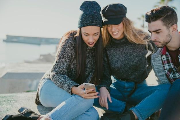 Друзья сидят у воды со смартфоном