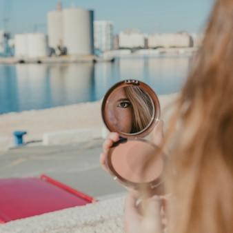 Девушка смотрит в маленькое зеркало перед гаванью