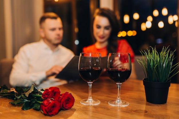 食事を持つ若いカップルのワイングラス