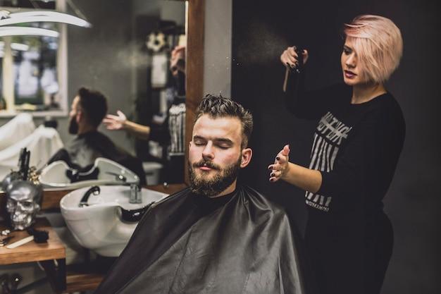 Женщина, используя спрей на человека в парикмахерской