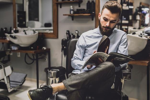 スタイリッシュな男性と理髪店での雑誌