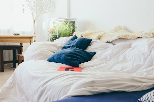 ノートブックとベッドの上に横たわる枕