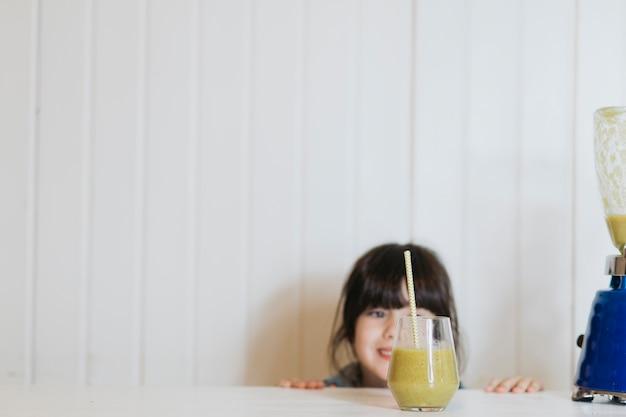 おいしいスムージーのガラスを持つ少女