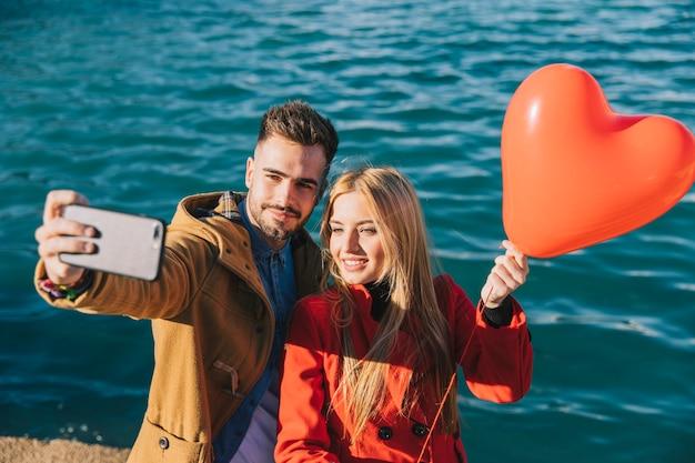 Веселая пара, берущая себя с воздушным шаром