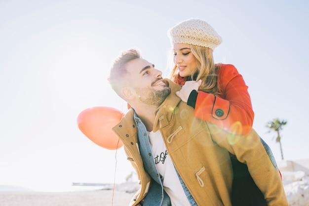Влюбленный мужчина с девушкой на спине