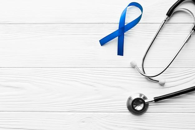 Синяя лента и стетоскоп на фоне пиломатериалов