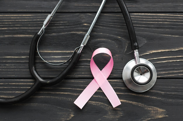 Розовая лента и стетоскоп на темном фоне