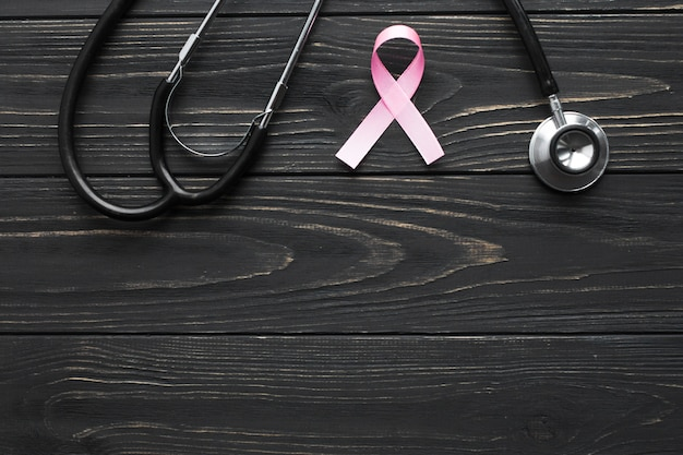 Стетоскоп и розовая лента на темном столе