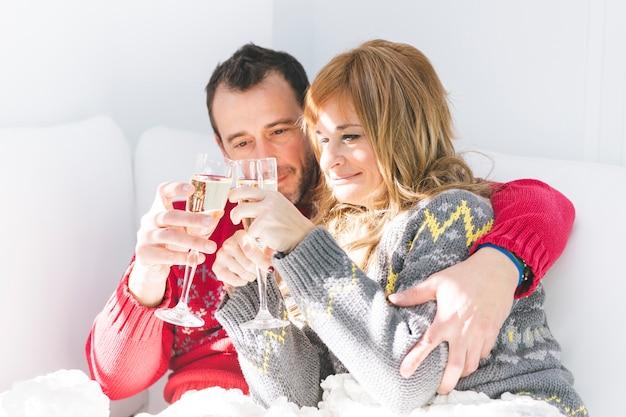 Пара звон бокалов с шампанским на диване