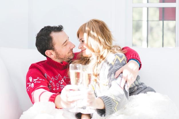 Праздничная пара счастлива с шампанским на диване