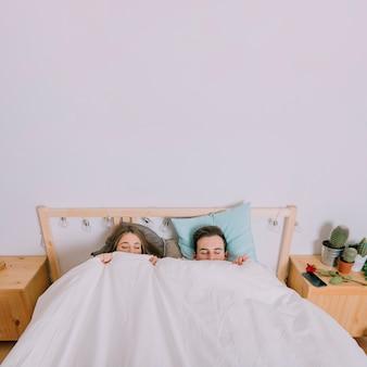 毛布の下に横たわっている甘いカップル