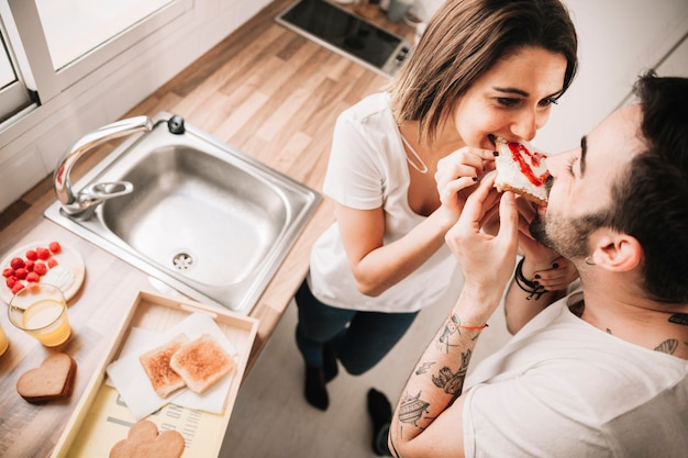 トーストを一緒に噛む朗らかなカップル