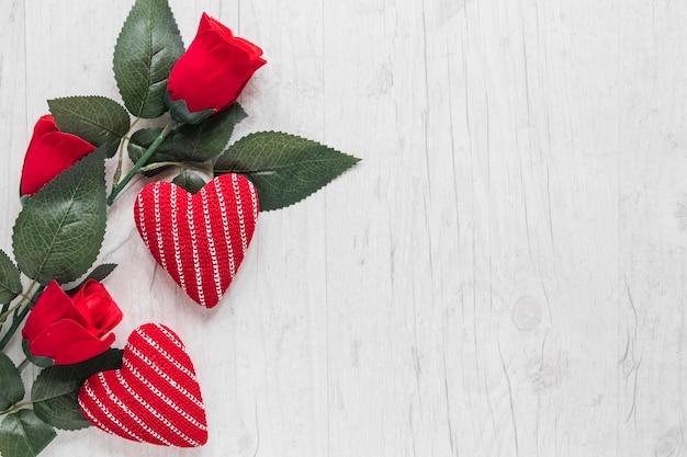 Розы и трикотажные сердца на деревянном фоне