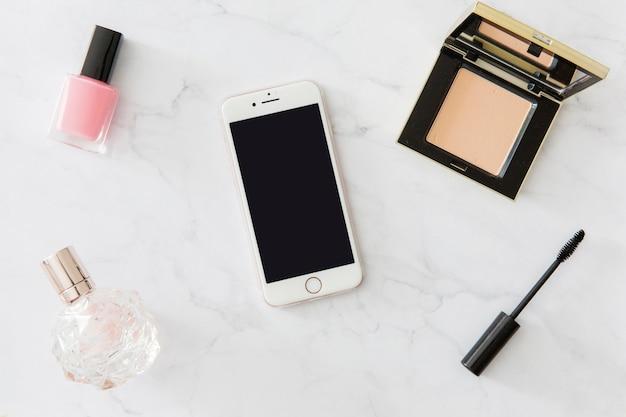 スマートフォンの周りの化粧品と香水