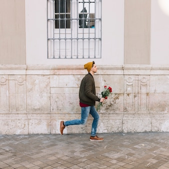 Человек с букетом, бегущим по улице