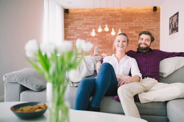 Улыбающиеся мужчина и женщина, сидя на диване