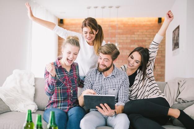 Возбужденные люди счастливы с триумфом, смотрящим планшет