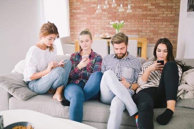 Группа людей, использующих гаджеты на диване